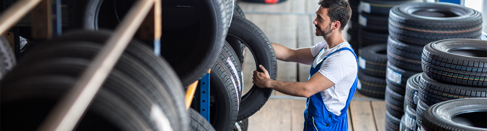 A mechanic grabbing a tyre from his stock - Tyres Loughborough